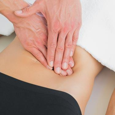 doctors hands on patient's stomach checking for IBS