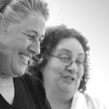 photo of two older women, smiling, working in Dr. Erber's office